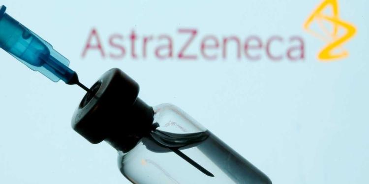 Frasco e seringa em frente ao logo da AstraZeneca em foto de ilustração