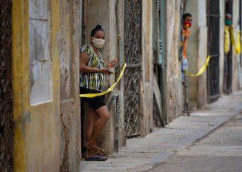 Cubanos nas portas de suas casas em área restrita após avanço de casos de Covid-19 em Havana