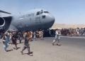 Imagens mostram cidadãos invadindo uma pista de decolagem e tentando se equilibrar nas rodas de uma aeronave militar